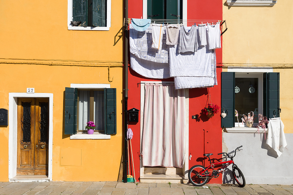 traditional houses in burano are painted in bright colours and can be seen with laundry hanging outside
