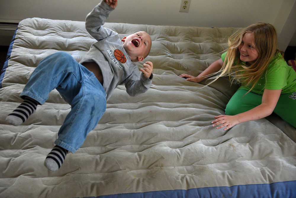Brodee Davis, 3, shoots in the air after his sister Melanie Otten, 9, flops down on an air mattress in her bedroom on their first day in a new apartment in Claremont, N.H. Thursday, June 4, 2015. Davis and Otten had been living with their parents Marsha Barger Alexander and Elijah Alexander in Claremont's homeless shelter and the family was given housewares and clothing by the aid organization Baby Steps on their move-in day. (Valley News - James M. Patterson)<br /> Copyright &copy; Valley News. May not be reprinted or used online without permission. Send requests to permission@vnews.com.