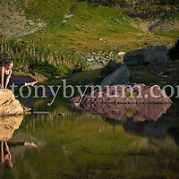woman doing yoga on rock in lake with reflection in mountains