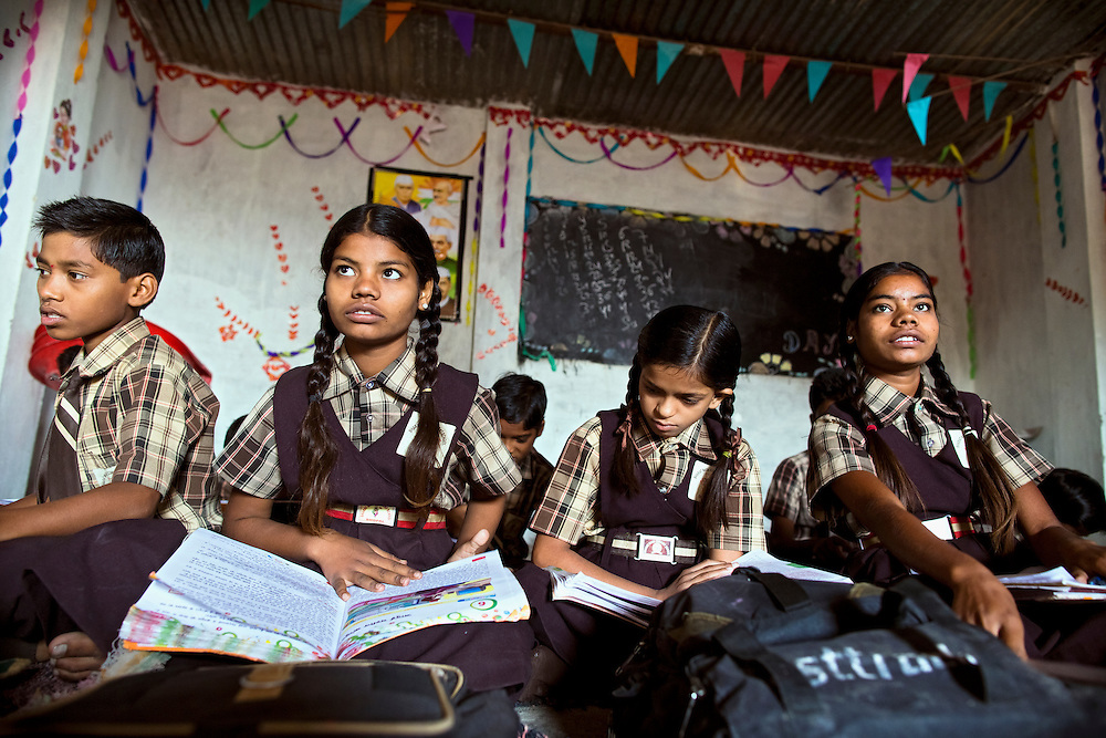 Poonam, 12, (left) is attending lessons with her sister Jyoti, 13, (right) on the floor of the cozy, private school they regularly attend since 2011, located by their newly built home in Oriya Basti, one of the water-contaminated colonies in Bhopal, central India, near the abandoned Union Carbide (now DOW Chemical) industrial complex, site of the infamous '1984 Gas Disaster'. The two girls are studying in Year 6, out of 12, in 2015-16.