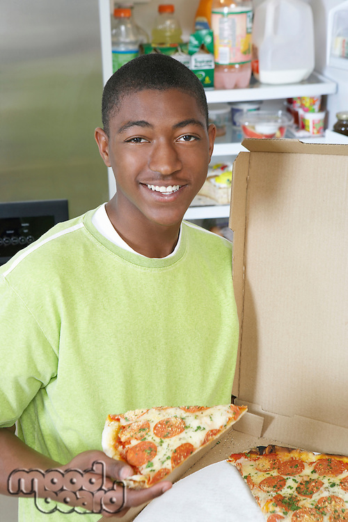 Young man eating pizza at home