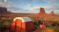 A camper relaxes at a campsite in front of the Mittens Buttes at Monument Valley, Arizona, shortly before sunset.