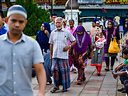 "22 AUGUST 2018 - GEORGE TOWN, PENANG, MALAYSIA:  Malaysian Muslims walk to Kapitan Keling Mosque in George Town for Eid al-Adha services. It is the oldest mosque in George Town. Eid al-Adha, ""Feast of the Sacrifice"" is the second of two Islamic holidays celebrated worldwide each year. It honors the willingness of Ibrahim (Abraham) to sacrifice his son as an act of obedience to God's command.     PHOTO BY JACK KURTZ"
