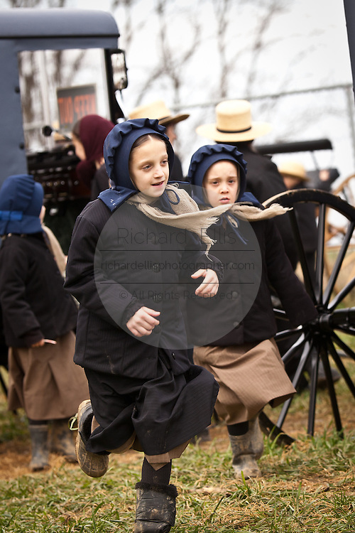Amish girls run during the Annual Mud Sale to support the Fire Department  in Gordonville, PA.