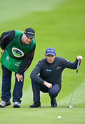 February 12, 2010; Pebble Beach, CA, USA; Padraig Harrington discuss a putt with caddy Ronan Flood on the first hole during the second round of the AT&T Pebble Beach Pro-Am at Pebble Beach Golf Links.