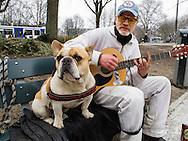 Nederland, Amsterdam, 10 april 2013<br /> Muzikant met zijn hond op een bankje op het weteringplantsoen. Volgens eigen zeggen is hij alcohollist. Zijn hond en gitaar zijn zijn belangrijkste bezit. <br /> Foto(c): Michiel Wijnbergh