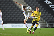 Milton Keynes Dons midfielder Conor McGrandles (18) heads the ball during the EFL Trophy match between Milton Keynes Dons and Coventry City at Stadium:MK, Milton Keynes, England on 3 December 2019.