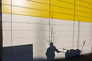 Morning shadows of a Lambeth street sweeper on yellow and white panelled wall of new south London housing.  Whilst known mainly for large high-profile schemes, Skanska also undertake many smaller projects including public realm improvements, involved in some of the UKs most prestigious projects in both the Private and Public Sectors.