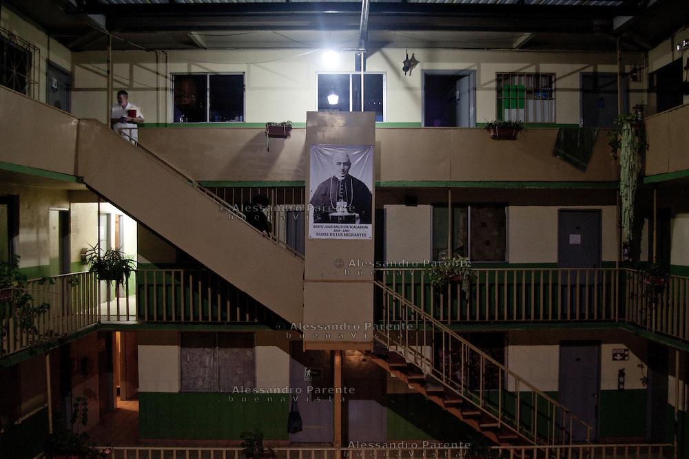"""Padre """"Pat"""" Murphy direttore della casa del migrante. Nel poster, Beato Giovan Battista Scalabrini, il missionario italiano che istitui' la casa del migrante."""