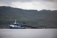 A maintenance vessel working at cages at a salmon farm on the west coast of Scotland.<br /> <br /> Photograph © Colin McPherson, 2019 all rights reserved