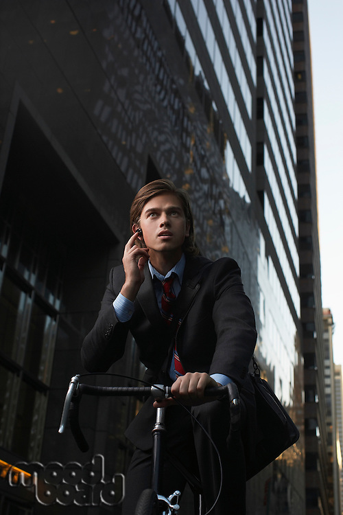 Man standing by bicycle in street talking on mobile phone low angle view