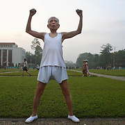 An elderly man exercises at dawn outside the Ho Chi Minh Mausoleum in Hanoi, Vietnam. As Vietnam's cities grow more affluent, nouveau-riche are taking up yoga and golf, replacing activities like tai chi and badminton.