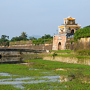 A bridge spans the moat at the Imperial City in Hue, Vietnam. A self-enclosed and fortified palace, the complex includes the Purple Forbidden City, which was the inner sanctum of the imperial household, as well as temples, courtyards, gardens, and other buildings. Much of the Imperial City was damaged or destroyed during the Vietnam War. It is now designated as a UNESCO World Heritage site.