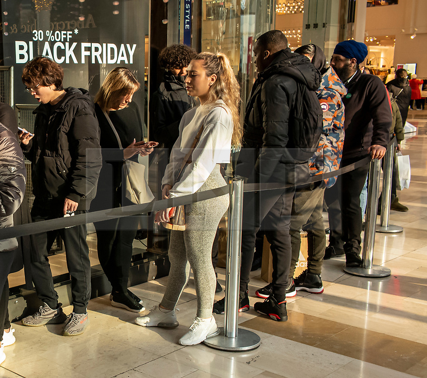© Licensed to London News Pictures. 29/11/2019. London, UK. Shoppers queue at Adidas on Black Friday at Westfield West London, as thousands of stores across the country are slashing prices to entice shoppers for Black Friday. Photo credit: Alex Lentati/LNP