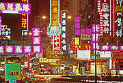 Neon signs glow on Kowloon, Hong Hong street