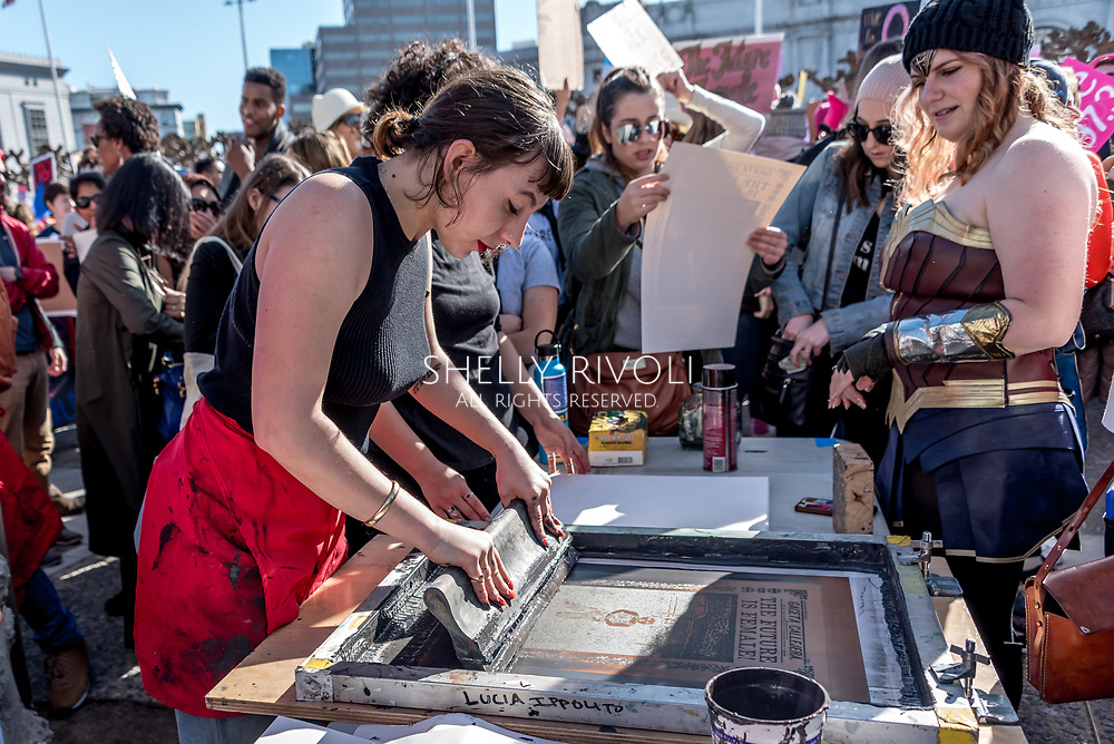 San Francisco, California, USA. 20th January, 2018. The 2018 Women's March in San Francisco, organized by Women's March Bay Area. A woman from the Poster Syndicate San Francisco creates commemorative posters for the events free for marchers.
