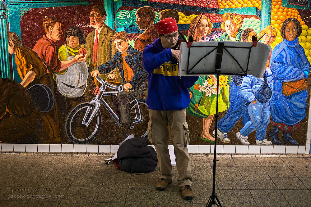 Man playing violin in front of mosaic mural, Times Square subway station, New York, NY, US