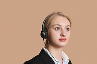 Beautiful female customer service representative over colored background