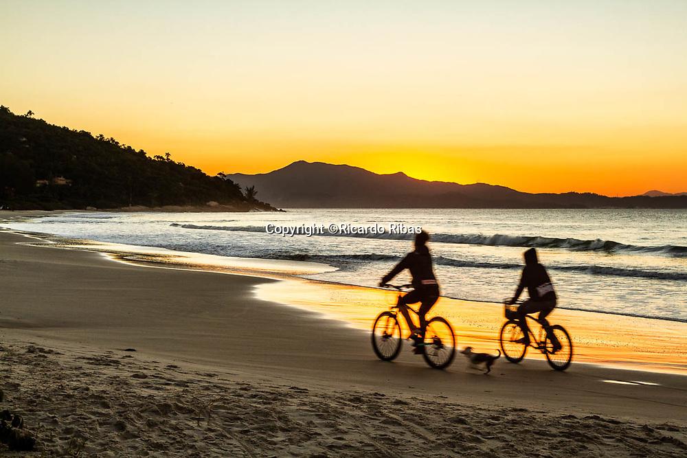 Silhueta de pessoas andando de bicicleta ao por do sol na Praia da Lagoinha. Florianópolis, Santa Catarina, Brasil. / Silhouette of people riding bicycles at Lagoinha Beach. Florianopolis, Santa Catarina, Brazil.