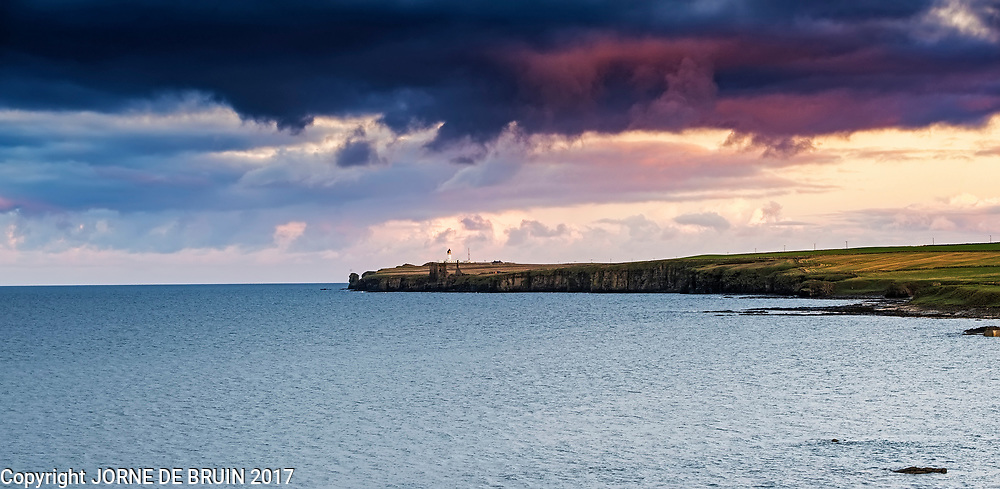 Noss Head and it's lighthouse against the setting sun on the northern coast of Scotland.