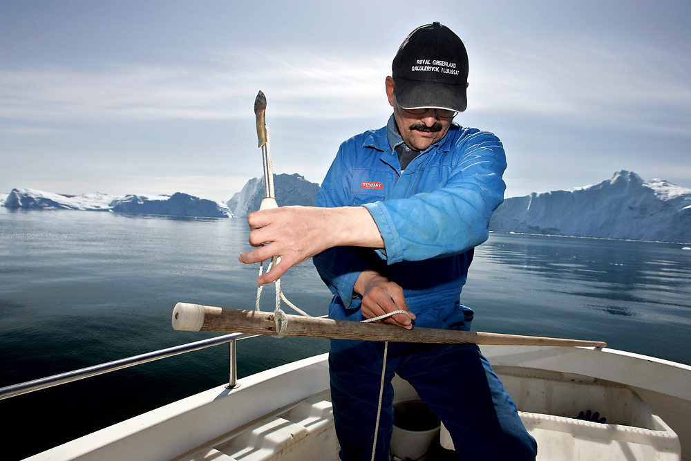 Gerth Gundel readies his harpoon while fishing between the icebergs in the Disko Bay. He is worried about the rising temperatures, the influx of freshwater in the oceans from the melting glaciers, the potential of changing ocean currents.<br />