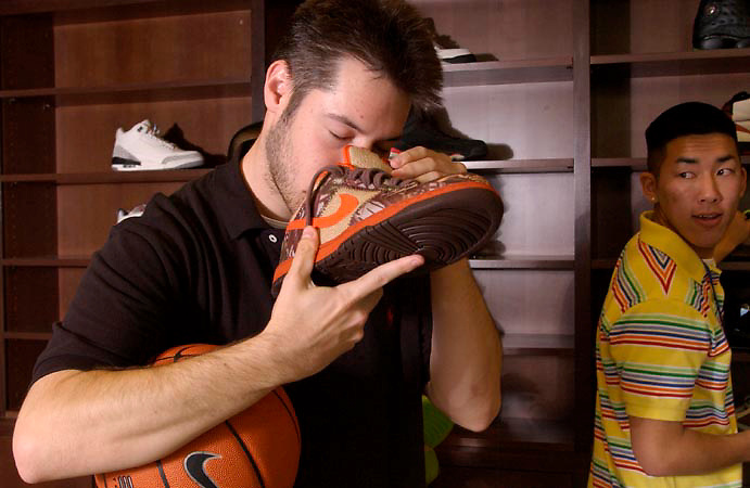 Seth Wollman takes a moment and uses the sense of smell to absorb himself in the shoe culture as Aaron Chiang glances over and shares in the experience.
