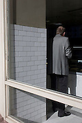 A man wearing a gret suit stands with his back to a shop window in central London.