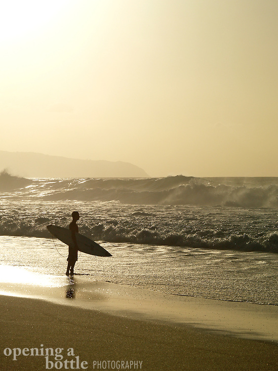 A surfer stares out into the breakers at the Bonzai Pipeline, North Shore of Oahu, Hawaii.