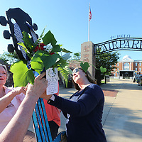 Tupelo Garden Club members Margaret Gratz, left, and Holly Walker hang a small flower arrangment on the guiter at Fairpark Thursday morning as a gift from the club along with other flower decorations located around downtown for this weeks Elvis festival and also to promote National Garden Week.