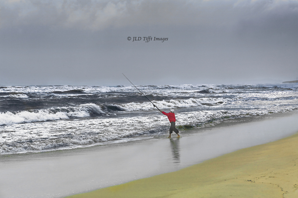 Solitary fisherman fishing in heavy surf on the beach north of Danang, Vietnam.  He stands poised just at the top of his cast, arm and rod outstretched.    Cloudy day, grey sky, a little yellow sand in the foreground; mirror reflections in the wet sand at the edge of the waves.  A feeling of man against the elements.