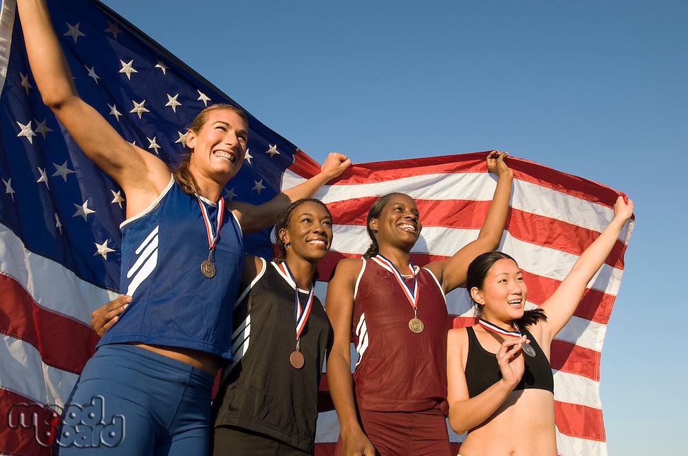 Four female athletes celebrating and holding american flag