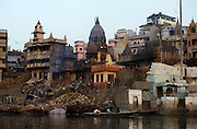 As the sun rises over the Ganges, the ghats are bathed in warm sunlight, Varanasi, Uttar Pradesh, India