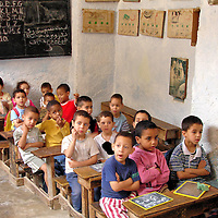 Grade School Children in Class in Fes el Bali at Fez, Morocco<br /> This photo of grade school children huddle together at wooden desks was not taken decades ago. Instead, this rudimentary classroom is located within the Fes el Bali. Morocco&rsquo;s official languages are Arabic and Tamazight. The latter is derived from the Berbers. French is also heard in the larger cities. However, notice the English alphabet on the blackboard. Despite limited resources, the teachers are trying to prepare their students to be multilingual.