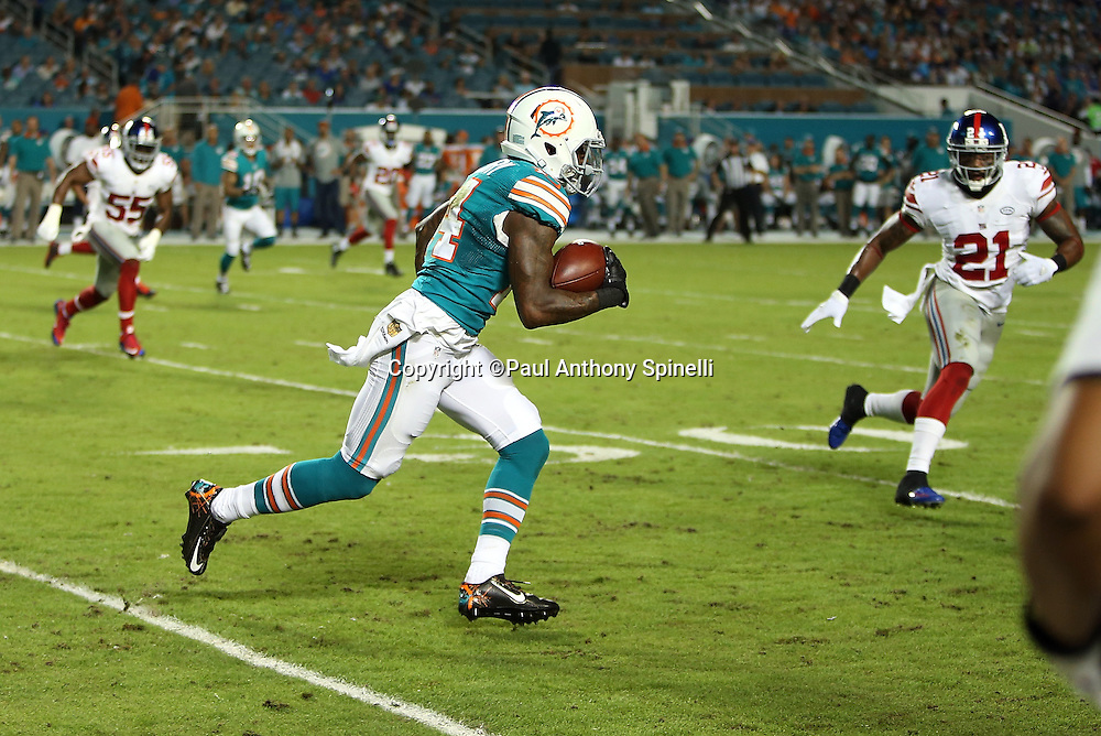 Miami Dolphins wide receiver Jarvis Landry (14) is chased by New York Giants free safety Landon Collins (21) after catching a first quarter pass for a first down during the NFL week 14 regular season football game against the New York Giants on Monday, Dec. 14, 2015 in Miami Gardens, Fla. The Giants won the game 31-24. (©Paul Anthony Spinelli)