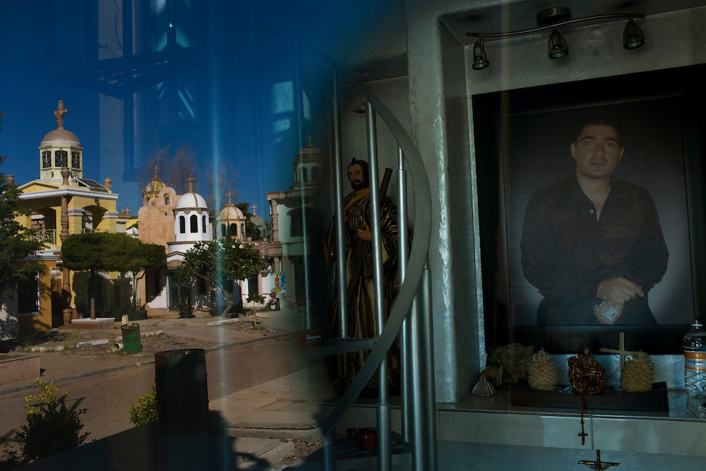"A photo of a deceased man is seen through the door of his memorial chapel, as the rest of the cematary is reflected in the door. Large chapels are built in the cematary in Culiacan, Mexico, known locally as the ""Pantheon"".  Some of the chapels, where the dead are buried, are two-story buildings complete with electricity and air conditioning.  This phenomenon, where people build increasingly large, luxurious memorials to their dead family members, is often associated with Mexico's Narco Culture."
