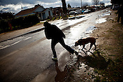 Maria Zapien and her dog, Shigo, jump over puddles with contaminated water that linger for days in the Parklawn neighborhood of Modesto, Calif., March 1, 2012.