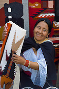 Indigenous woman selling hand woven rugs in marketplace, Otavalo, Imbabura, Ecuador