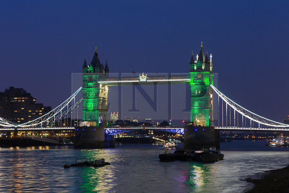 © Licensed to London News Pictures. 23/03/2016. London, UK. Tower Bridge is illuminated in GREEN, which is not one of the colours of the Belgian tricolor flag this evening, during an illumination to pay a tribute to victims of the Belgium terrorist attacks which took place yesterday. Landmarks across London are paying tribute this evening. Photo credit : Vickie Flores/LNP