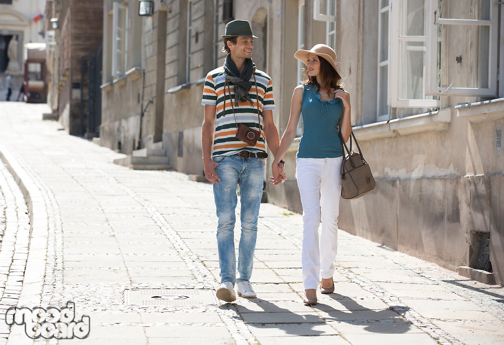 Tourist couple holding hands while walking on sidewalk