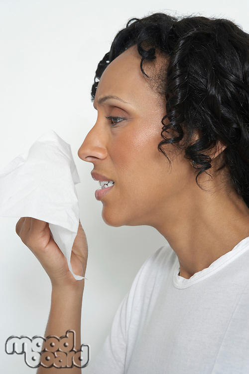 Woman holding tissue to face, studio shot