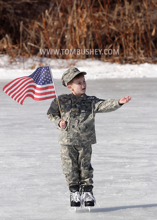 Livingston Manor, NY -Talon Miller holds an American flag during  the 49th annual Livingston Manor Rotary Ice Carnival on Jan. 27, 2008. Talon, his sister Suzanne and their mother Kimberlin Miller performed a tribute to their father, Maj. Joel Miller, who is serving in Iraq.