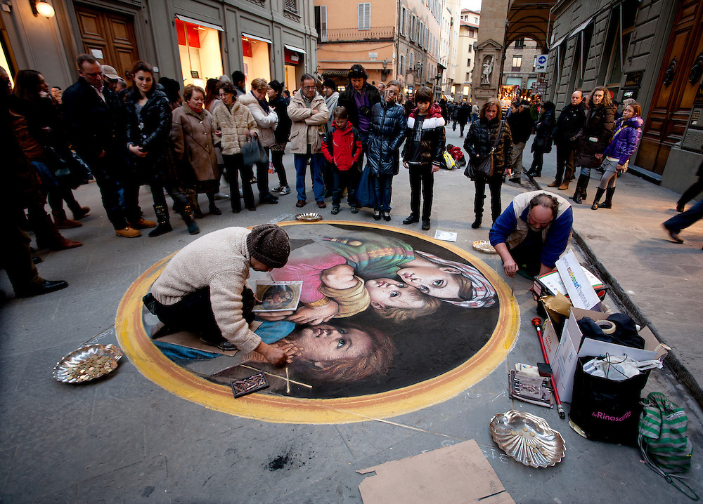 A pair of street artists working on a copy of a Raphael Madonna and child in the Pitti Palace.  Onlookers gather around.  Scallop-shaped dishes for offerings of money.  It is dusk so shop windows are lit.