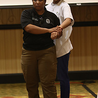 Lt. Katarsha White demonstrates a self-defense move on attendee Mariah Wilson, 13, Saturday at the G.I.R.L. Talk event