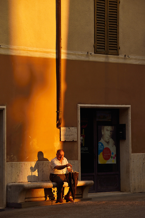 Old man with umbrella sitting on bench in square, town of San Quirico D'Orcia,Tuscany,Siena Province,Italy,Europe