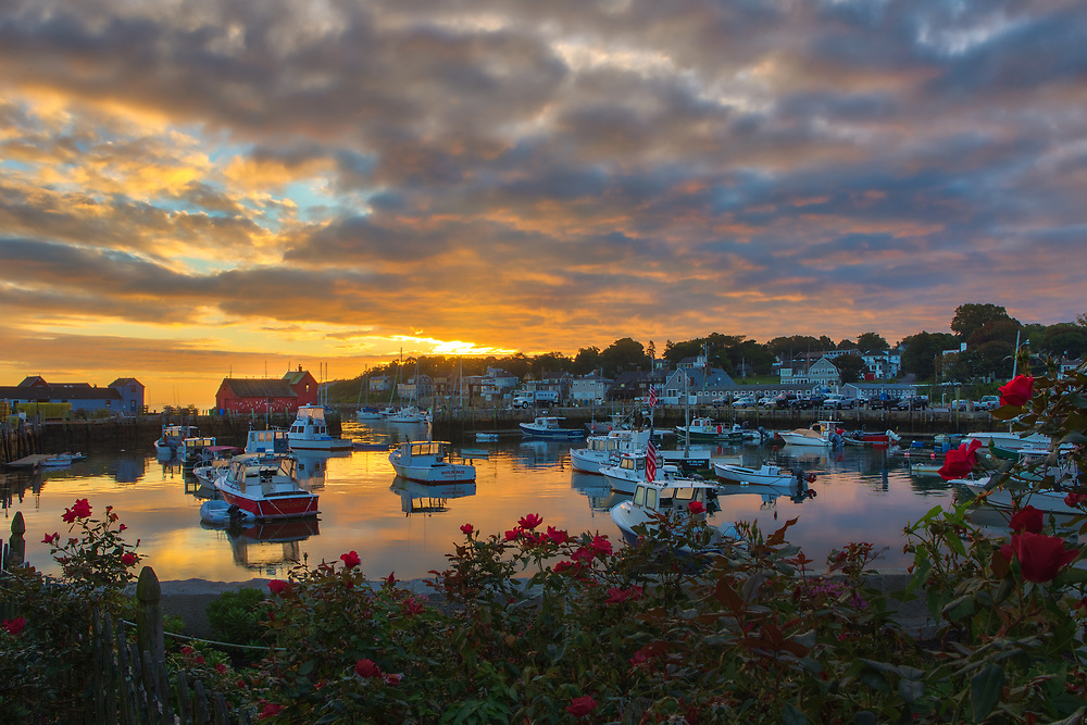 New England photography of Motif #1, a famous red fishing shack and historic landmark in Rockport, Massachusetts on Cape Ann. The photo captures the local fishing boats with the iconic landmark and a stunningly beautiful sunrise sky. The historic landmark is known throughout New England as Motif #1, so called because it is the most often painted building in America.<br />