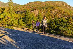"Three women hiking on ""The Beehive"" in fall in Maine's Acadia National Park.`"