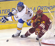 LSSU's Rick Schofield (23) and Ferris State's Matt Case (16) chase a loose puck around the Ferris net during Saturday nights game at Taffy Abel Arena in Sault Ste. Marie.