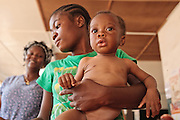 Leona Hunter, 18, holds her son Cephas Hunter, 10 months old, who suffers from severe malnutrition, as she waits to have him measured during growth monitoring at the Slipway clinic in Monrovia, Montserrado county, Liberia on Monday April 2, 2012.