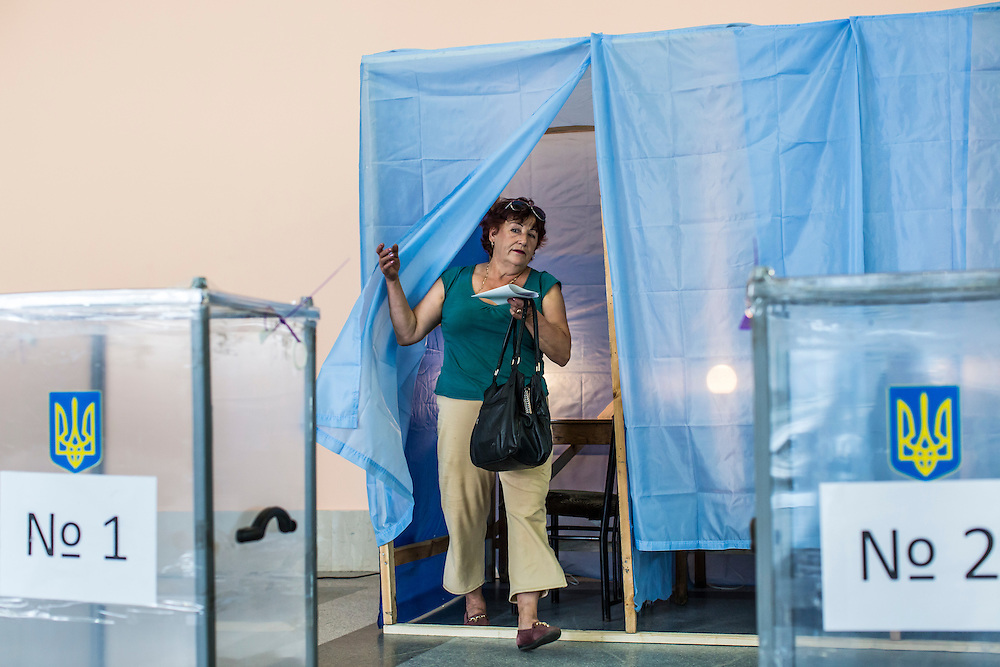 KRASNOARMIISK, UKRAINE - MAY 25:   A woman at a polling station emerges from a voting booth after filling out her ballot in Ukraine's presidential election on May 25, 2014 in Krasnoarmiisk, Ukraine. The elections are widely viewed as crucial to taming instability in the eastern part of the country. (Photo by Brendan Hoffman/Getty Images) *** Local Caption ***