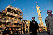 Two men are walking by a mosque and a building still showing signs of the 2004 US-led battles on the streets of Fallujah, Iraq.